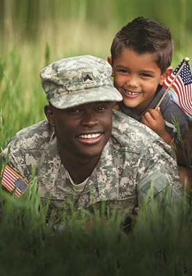 US Army Soldier and young boy who is holding an American Flag.